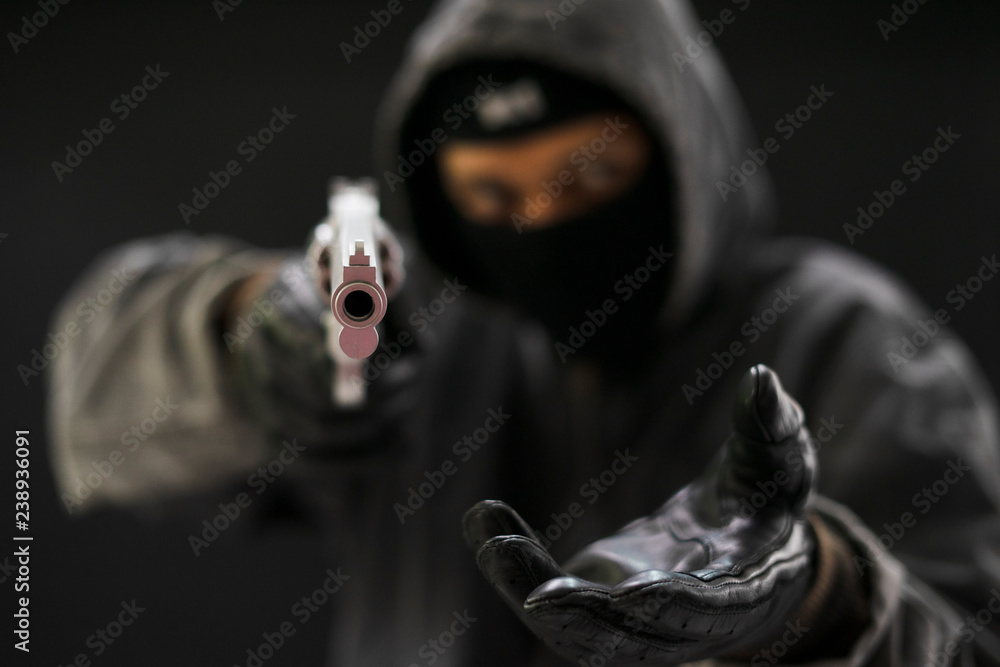 Fototapeta Robber with a gun robbing intimidate.Crime and robbery concept.