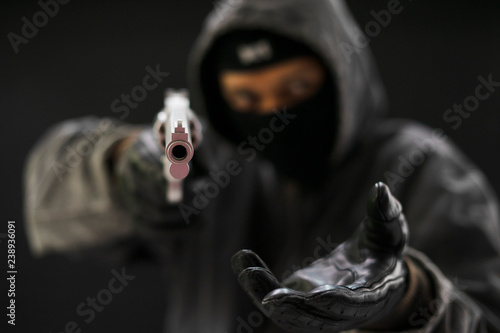 Robber with a gun robbing intimidate.Crime and robbery concept. Canvas Print
