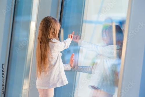 Fototapeta Little girl in airport near big window while wait for boarding obraz na płótnie