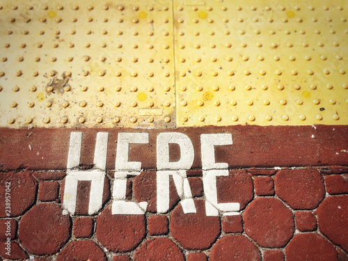 Fotografía  Word HERE painted on to rust colored paving stones.