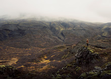 Woman Standing On A Mountain C...