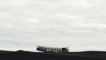 Derelict Aircraft Sitting On A Black Volcanic Sand Beach
