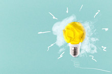 Crumpled Yellow Paper Light Bulb On A Blue Background With Smoke, Concept Idea