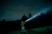 Man Searching With Flashlight In Outdoor By Night