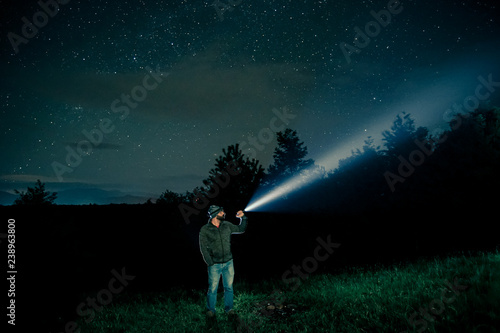 Obraz Man searching with flashlight in outdoor by night - fototapety do salonu