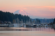 Mt Rainier In Seen In The Little Town Of Gig Harbor In Washington State, Boats And Ships In The Harbor Frame The Mountain