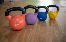 Colorful Kettlebells In A Row On Floor In A Gym, Orange,  Violet, Blue, Yellow,