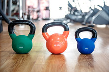 Colorful Kettlebells In A Row On Floor In A Gym, Green, Orange, Blue,