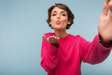 Young Beautiful Woman With Dark Short Hair In Pink Sweater Sending Air Kiss Dreamily Looking In Camera While Taking Photo Over Blue Background