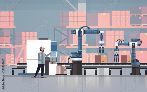 Obraz man engineer controlling conveyor belt line robotic hands factory automation production manufacturing process concept warehouse storage interior horizontal - fototapety do salonu