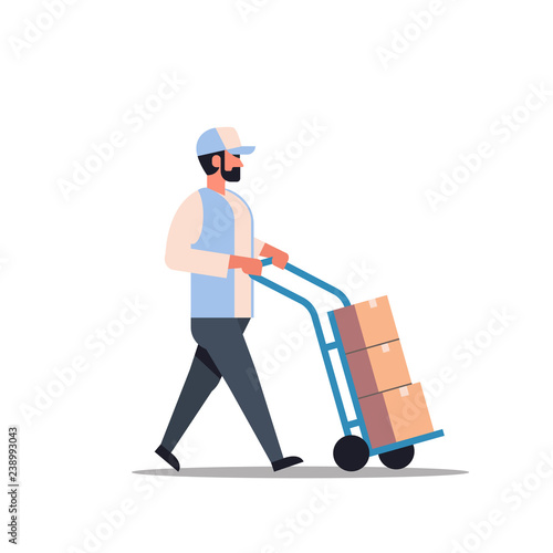 Fototapeta delivery man rolling cardboard box cargo trolley pushcart courier carrying parce