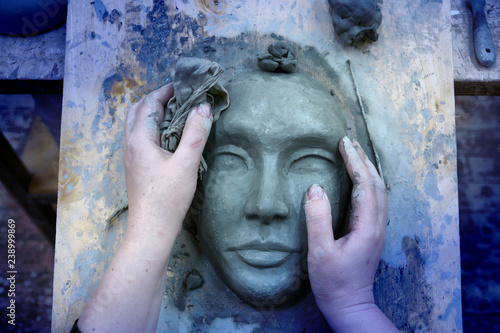 Carta da parati The hands of the sculptor mold the clay mask