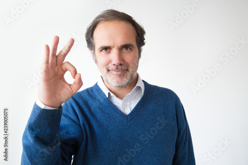 Valokuva  Positive Caucasian man showing ok sign