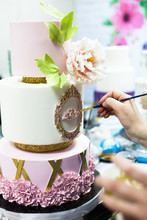 Decorating Tiered Mastic Weeding Cake With Flowers And Colouring Details By Brush