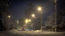 Beautiful Rural Winter Snow-covered Street With Lanterns On. And Light Trails From Cars