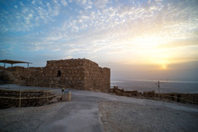 Ancient Fortress Of Masada At Dawn. The Ruins Of An Old Jewish Fortress In The Desert. Sightseeing In Israel. Archaeological Excavations. Sunrise In The Cloudy Sky Over The Dead Sea.