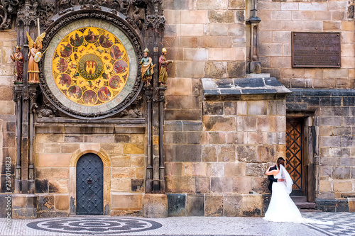 Fotografía  the bride and groom on the background of the famous astronomical clock in Prague