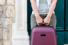 Girl Traveler Holds Suitcase In Her Hands. Woman Tourist Stands Near Door Of Authentic Hotel Or Apartments In Old Town. Concept Of Travel, Vacation, Solo Female Tourism, Trip, Adventure.