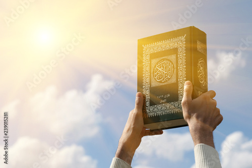 Photo Man's hands holds Koran - holy book of muslims, on blue sky with clouds