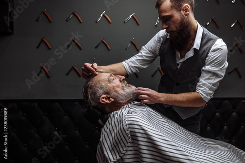 Fényképezés  Caucasin old man getting his beard shaved by barber visiting hairtician at shaving saloon