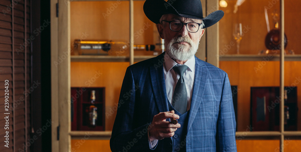 Foto  Stylish old-aged dandy in wide brimmed hat and rich dark blue mens suit smoking cigar indoor, standing near the bar counter with alcohol drinks