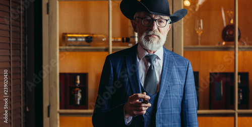 Stylish old-aged dandy in wide brimmed hat and rich dark blue mens suit smoking cigar indoor, standing near the bar counter with alcohol drinks Fotobehang
