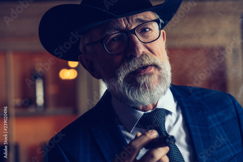 Thoughtful, selective, male aged investor in glasses, smoking cigar, fume, hold Fotobehang