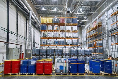 Poster de jardin Bat. Industriel Oil drums and plastic container on pallets in a warehouse on metal shelving. Handling and storing industrial lubricants. Hazardous material storage. Red and blue tank