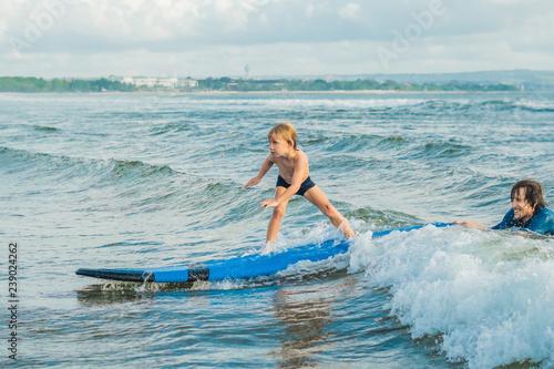 Fotografía Little boy surfing on tropical beach