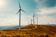 Leinwandbild Motiv Wind turbines on beautiful sunny summer autumn mountain landsape. Curvy road through mountain Eolic park. Green ecological power energy generation. Wind farm eco field