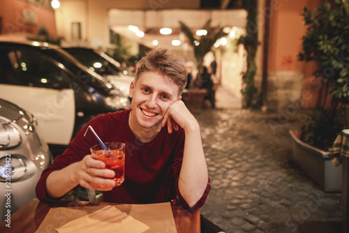 Fotografía  Portrait of a smiling young man who sits in the evening in a restaurant with a glass of alcohol in his hands,looks camera