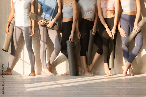 Six slim females wearing sportswear sports tops and leggings standing barefoot near wall in row holding yoga mats, women body without faces, sunlight through window in the morning. Wellness concept