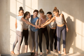 Beautiful sporty women standing barefoot ready for yoga session at gym in sunny day. Diverse beautiful slim girls putting stacked holding hands together, gesture of respect trust and support concept