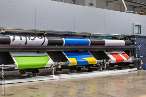 Fototapeta Very big printer during color sample phase, massive vinyl rolls, digital press technology, out of standard large advertising production. Automated process concept.  obraz