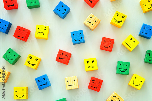 Fényképezés  concept of Different emotions drawn on colorfull cubes, wooden background