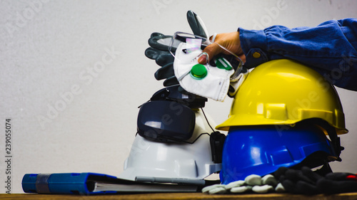 Photo Works safety concept: PPE (Personal Protective Equipment), hard hat or industrial helmet for protection the worker from accident during working at construction site, factory or industry building