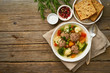meatballs soup in white plate on old wooden rustic grey table, top view