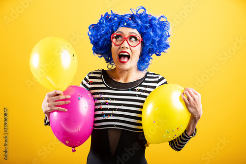 Photo  Cute Asian Woman playing with balloons and confetti wearing bright colorful wig