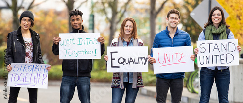 Group of five people holding signs with message of unity and equality