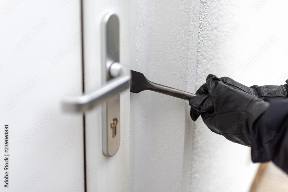 Fototapeta Einbrecher will mit einer Brechstange eine Haustür aufhebeln