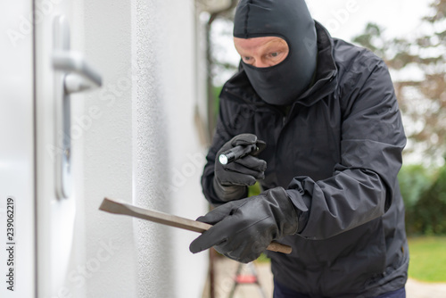 Canvas-taulu Einbrecher will mit einer Brechstange eine Haustür aufhebeln