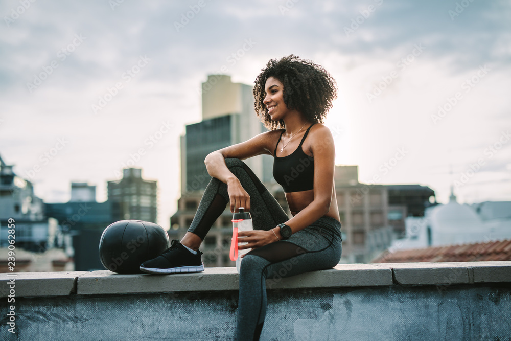 Fototapety, obrazy: Fitness woman sitting on rooftop taking break from workout