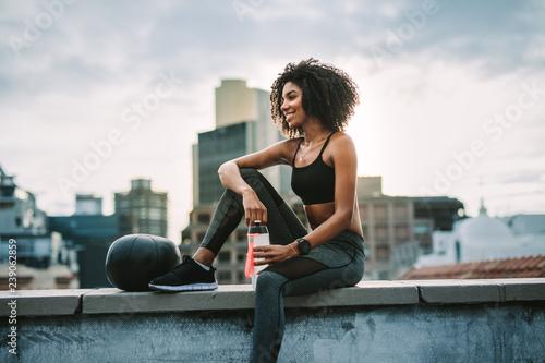 Fotografie, Obraz  Fitness woman sitting on rooftop taking break from workout