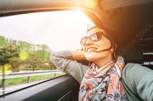 Leinwand Poster Woman enjoy with view from car window when traveling by auto