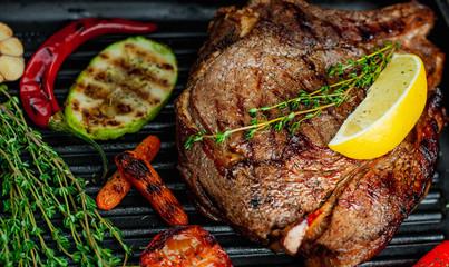 Fototapeta Do gastronomi grilled steak on a pan, close-up, lemon, red pepper, garlic and seasonings on a dark rustic background