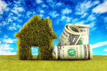 One Dollar Banknotes And Green Eco House Icon Concept With Grass And Blue Sky Background. Renewable Energy. Electricity Prices, Energy Saving In The Household.