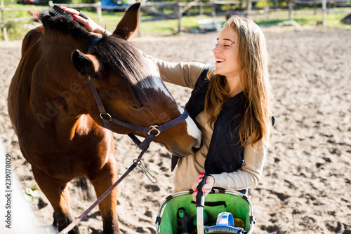 Girl equestrian rider equips horse. Horse theme