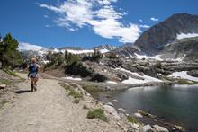 Female Hiker Walks Along The Trail Near Steelhead Lake Along The 20 Lakes Basin Area Of California Mountains