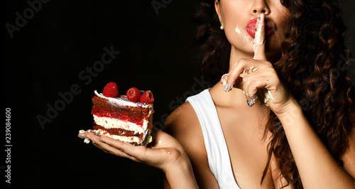 Young woman chef cook holding sweet piece cake with strawberry blueberry and cre Canvas Print