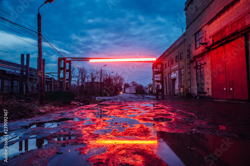 Photo Stands Old abandoned buildings Old industrial area at night. Dirty pools on cracked asphalt of damaged road